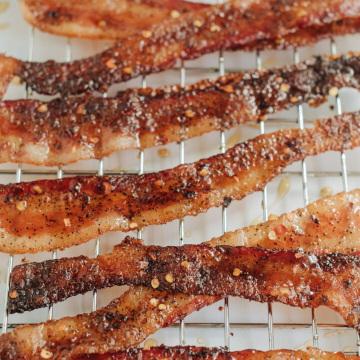 Candied bacon featuring pepper flakes and maple syrup on a baking rack