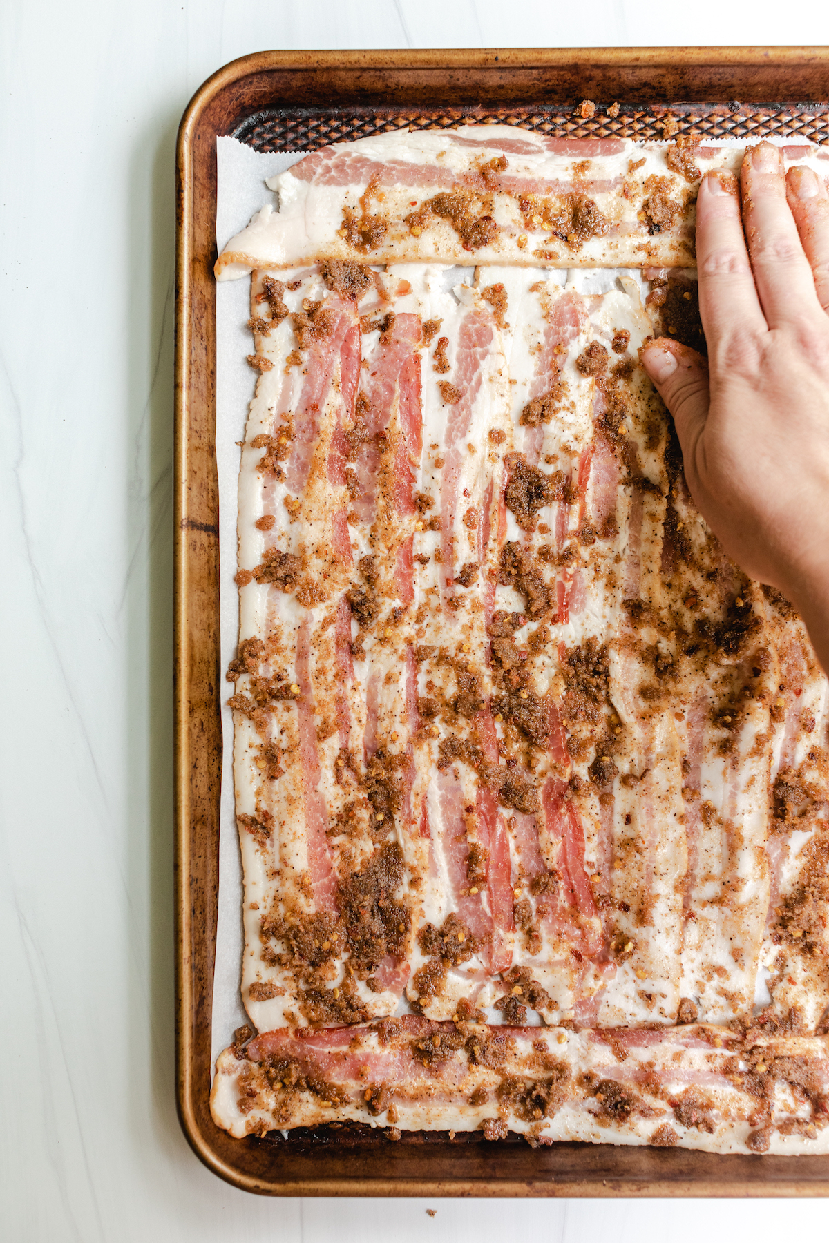 Hand spreading sugar and spice mixture over bacon on a baking sheet to make Million Dollar Bacon