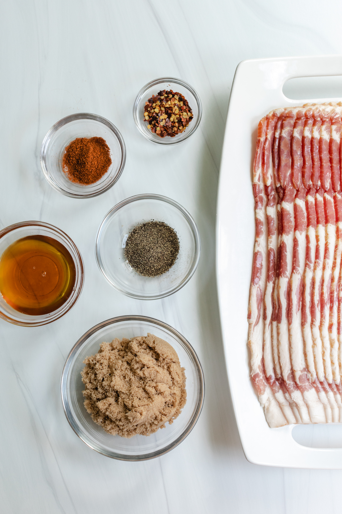 Thick cut bacon and assorted spices in prep bowls used to make Million Dollar Bacon