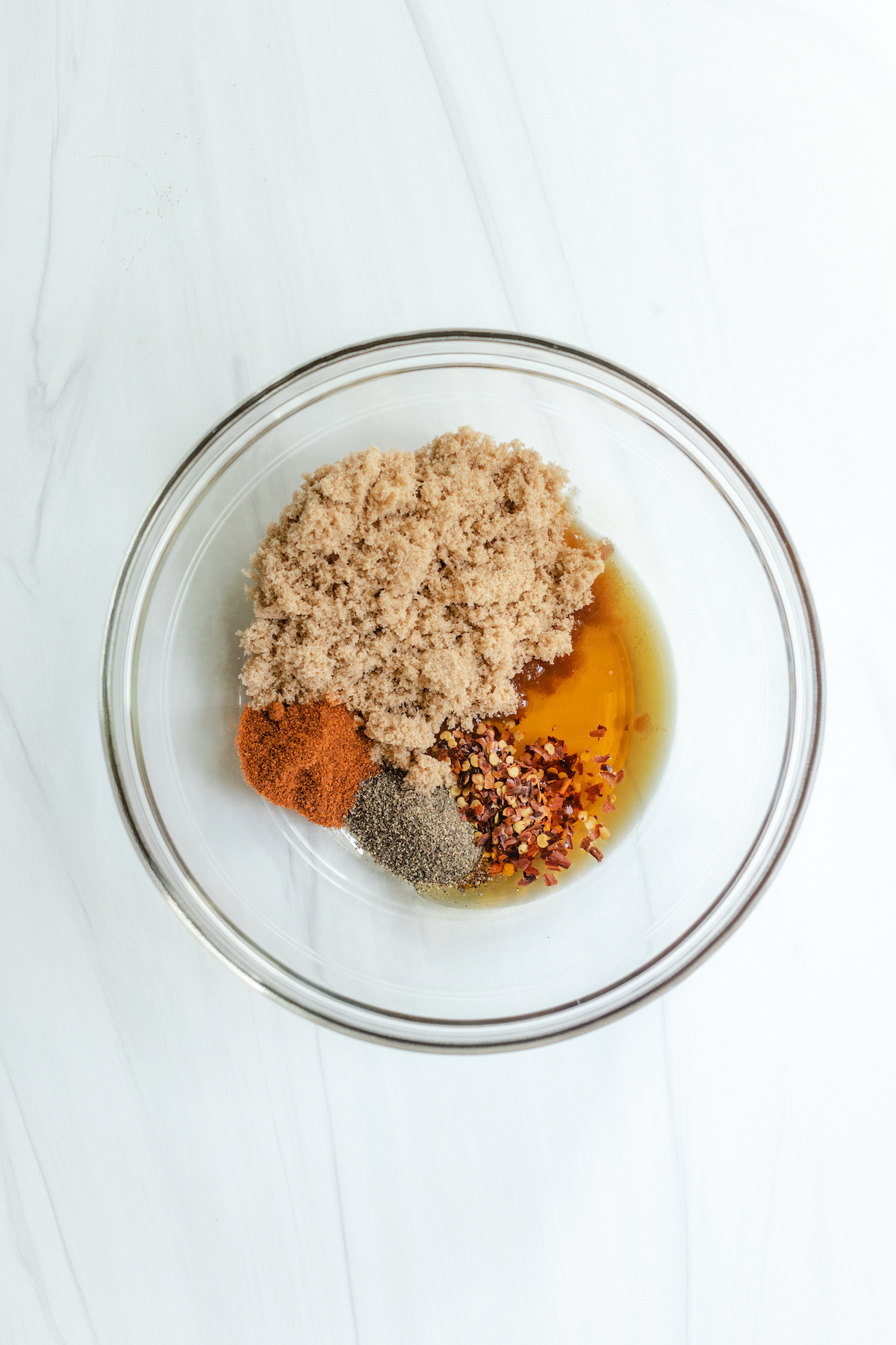 Spices, brown sugar and maple syrup in a glass mixing bowl - ingredients for Million Dollar Bacon