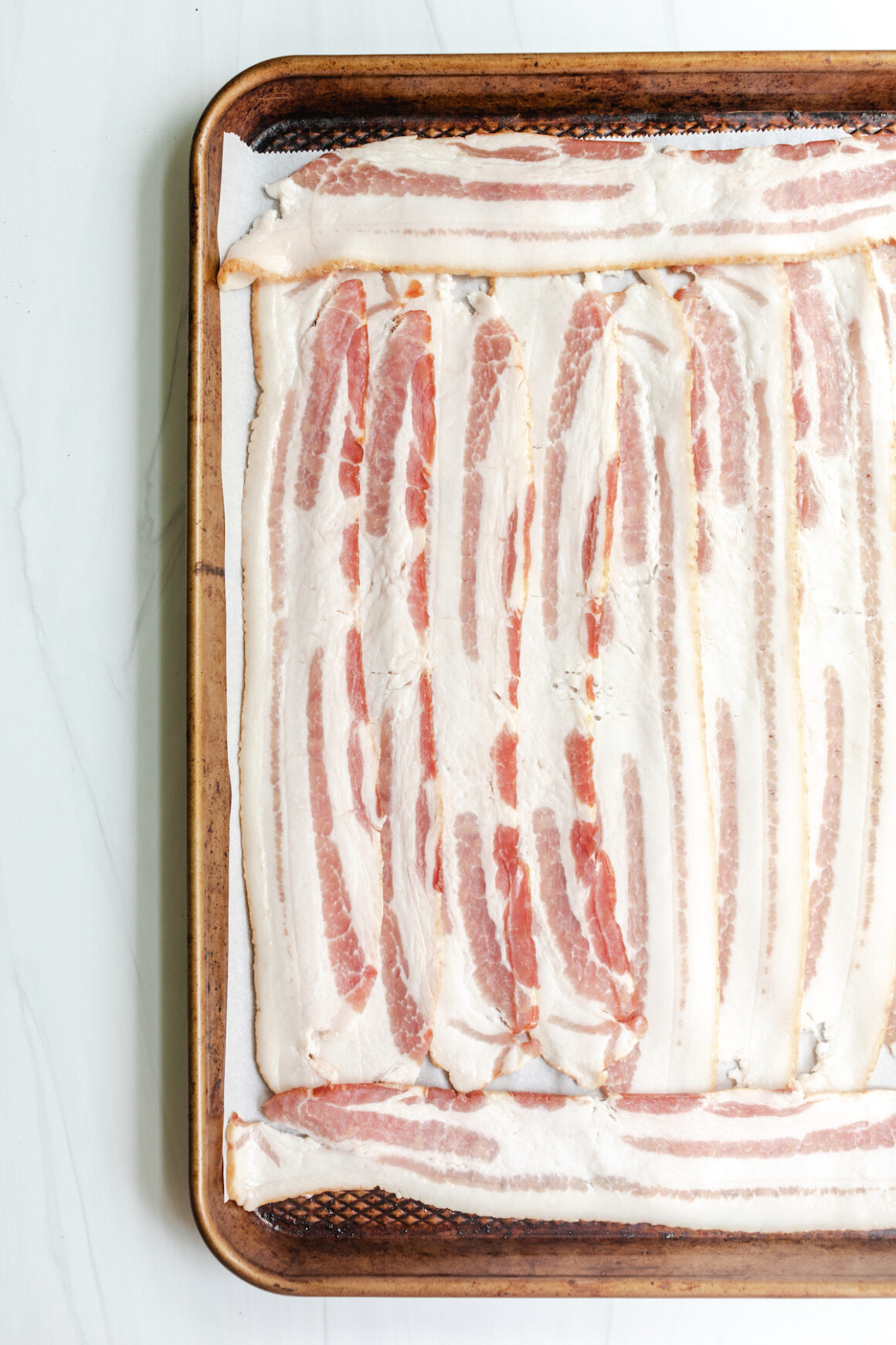 Thick cut bacon on a baking sheet with parchment paper