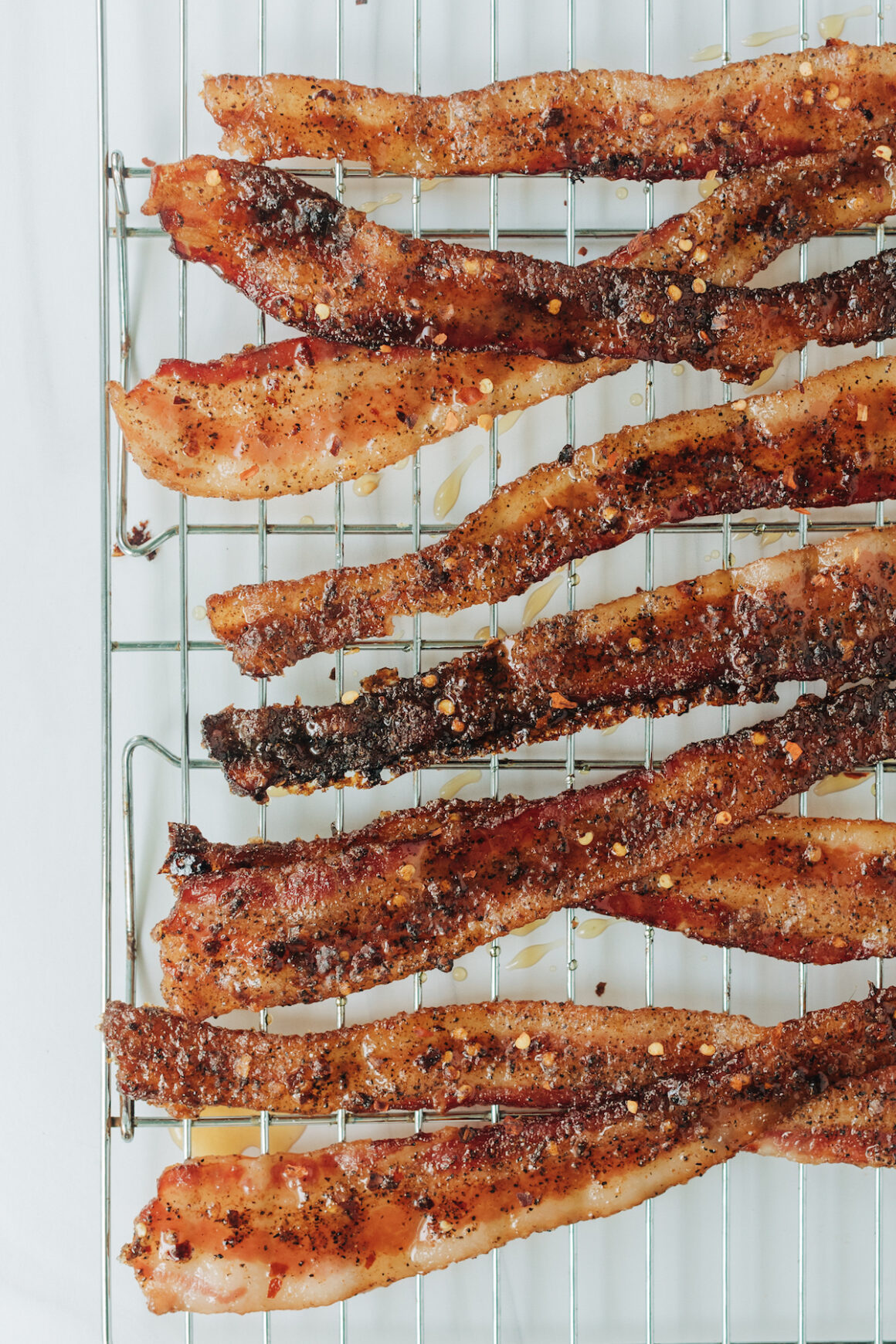 Crispy candied bacon with red pepper flakes on a baking rack