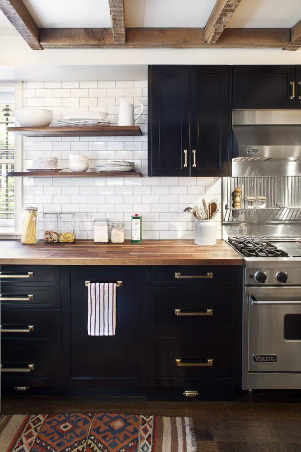 Kitchen with black cabinets, brass hardware, commercial range, subway tile backsplash, open shelving, butcherblock countertops