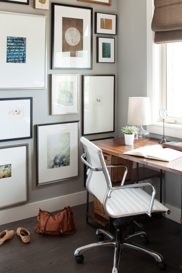 Office with gallery wall and warm wood floors